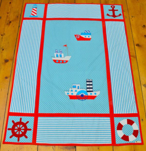 námořnická deka s obrázky parníků, majákem, kotvou, kruhem a kormidelm
